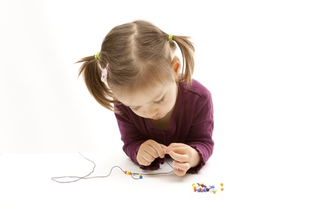 Cute little girl beading on isolated white background
