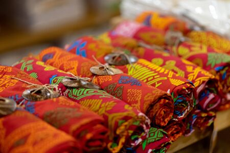 Traditional woven fabrics of various colors are displayed in a way rolled to attract tourists.