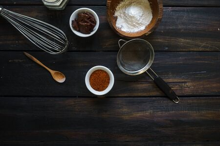 Kitchen utensils are arranged randomly on a dark wooden table.
