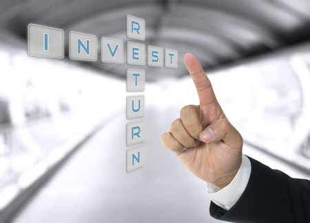 invest and return word with hand of business man Stock Photo