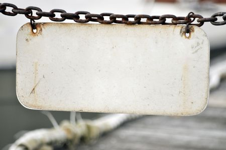 plate: old blank license plate hanging by a chain