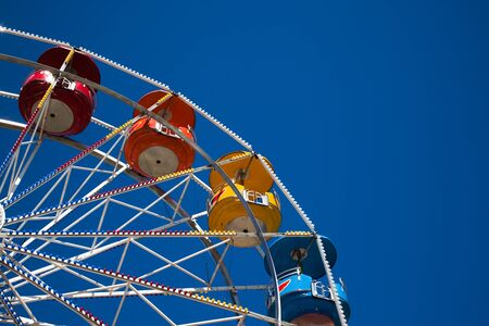 Rainbow colored cars on a large ferris wheel against a dramatic blue sky at the North Idaho Fair in Coeur dAlene. Stock Photo
