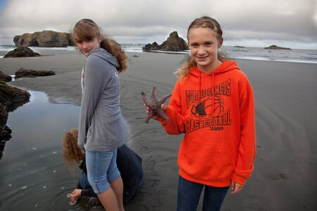 Gold Beach, Oregon, August 14 2010: A smiling young girl holds a starfish that she discovered while walking on the beach with her sister and mother. Editorial