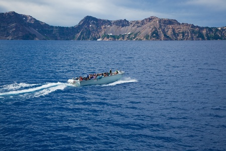 Crater Lake, Oregon, August 10, 2010: A boat full of tourists taking a ride on the deepest and bluest lake in the United States.