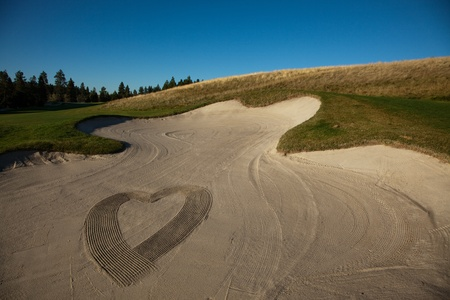 The shape of a heart made by a rake in a sand trap at a golf course.