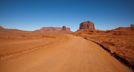 A red dirt road gives access to the impressive sandstone formations that create Monument Valley in the Navajo Nation. photo