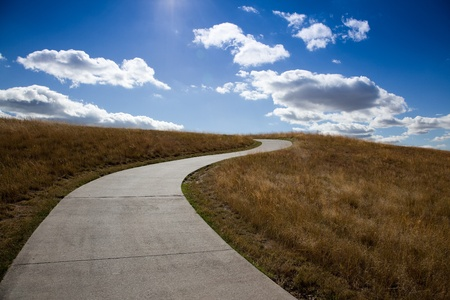 An empty golf cart path winds its way up a grassy hill towards the blue sky with fluffy white clouds and sunshine. Archivio Fotografico