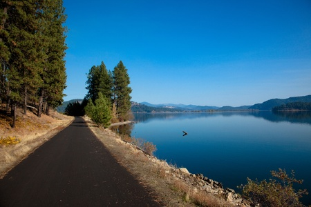 evergreen trees: A recreational trail leads its users past dynamic scenery of a clam blue lake framed with evergreen trees and distant mountains.
