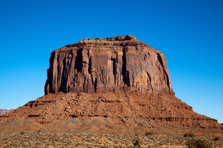 Merrick Butte, a massive eroding orange sandstone formation located on the Navajo Nation in Monument Valley, AZ, is illuminated by morning sun and surrounded by the bright blue January sky. Stock Photo - 9652850