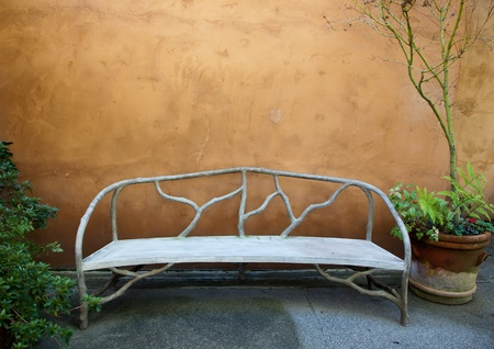 An empty bench made from concrete to look like wood branches sits in front of a stucco wall in a enclosed garden.