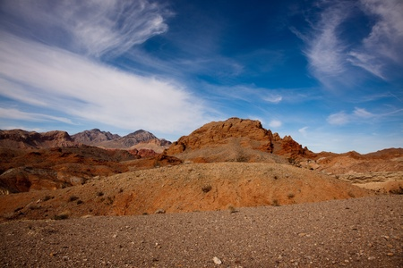 Miles of colorful rocky desert landscape stretch beneath the blue sky with wispy white clouds just north of Lake Mead, Nevada.
