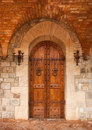 Sturdy European oak doors which are adorned by hand hammered iron accents and lamps are surrounded by masonry of chiseled stone, an arch of red brick, and a herringbone brick walkway.