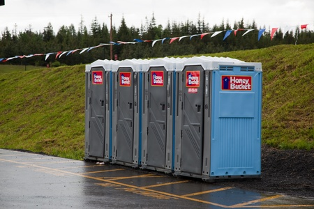 Coeur d'Alene Tribal Reservation, Fighting Creek, Idaho - June 13, 2011: A row of Honey Bucket porta potties stand ready to relieve lifes necessities in a no parking zone at Fighting Creek Store, Idaho. Editorial