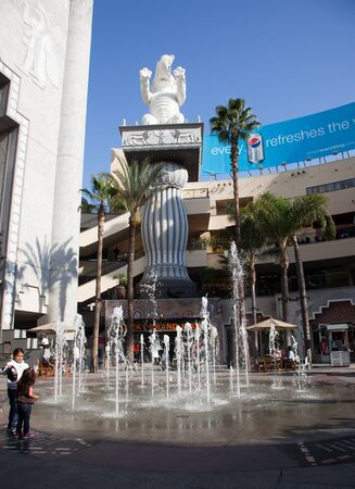 Hollywood, California - January 19, 2011: Center court of Hollywood and Highland Center open mall with a dancing water fountain, a elephant statue on a pillar, and people enjoying the summer like weather in January in Hollywood, California.