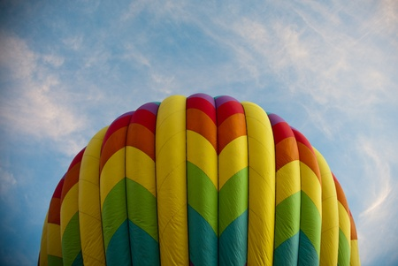 A colorful hot air balloon is in the final stages of inflation with the early morning sun highlighting the right side and a blue sky background.