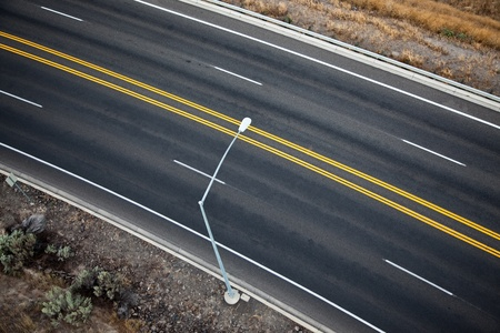A single street light on an empty four lane road divided by two yellow lines as seen from a hot air balloon. Stock Photo
