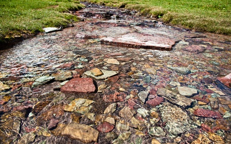 Pure, clean glacier water runs over colorful rocks in a peaceful flow at Glacier National Park, Montana. Stock Photo - 10692491
