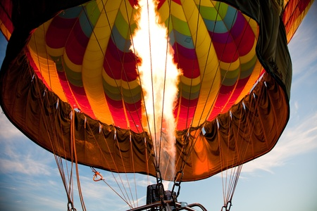 A burner with its super hot flame light up the inside of a colorful hot air balloon as it is inflated for an early morning flight. Editoriali