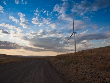 A giant windmill stands on the side of a gravel road which winds through a barren landscape that contrasts with dramatic clouds and blue sky in the late afternoon. Stock Photo
