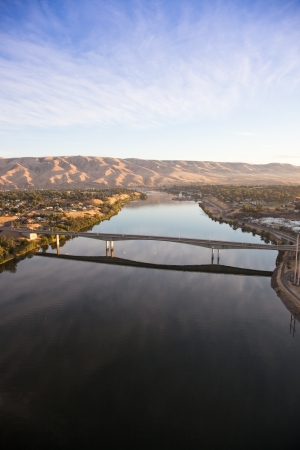 An early morning areal view from a hot air balloon of the Southway Bridge over the Snake River with Clarkston Washington on the left, and Lewiston Idaho on the right. Stock Photo