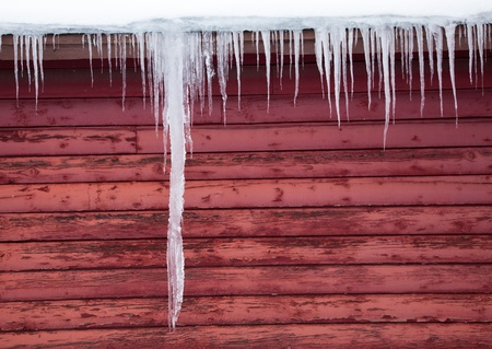 A giant icicle hangs down the side of a red wood barn with other icicles along the eaves.