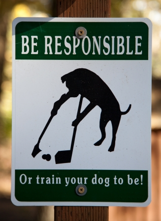 poop: A humorous sign posted for pet owners to pick up after their dogs.