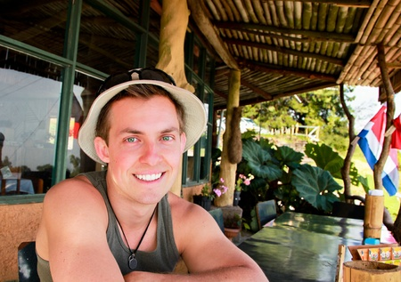 A young man with a big smile and green eyes sits outside at a local restaurant in Costa Rica.