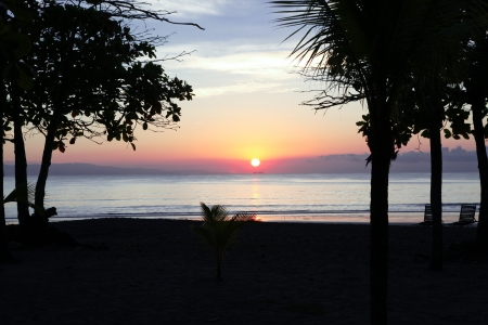 The first rays of a pastel sunrise give just a hint of light to an empty tropical beach in Costa Rica.