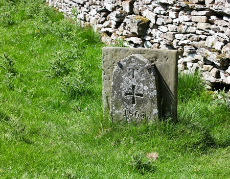 knights templar: A limestone tablet by a stone fence in the English countryside marks a cemetery entrance for the Knights Templar crossed dated 1865. Stock Photo