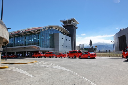 San Jose, Costa Rica - January 14: A line of redish orange taxi cabs wait in line outside of the front entrance of San Jose International Airport, Costa Rica.