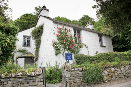 Grasmere, Cumbria, England - June 21: Climbing roses are in bloom against the home of poet William Wordsworth which is now a museum in Grasmere, Cumbria, England.