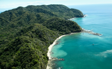 Lush jungle covered mountains stretch out into the Gulf of Nicoya next to the rocky and sandy beach of Ballena Bay in Costa Rica.