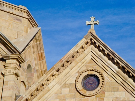 The steep roof lines of The Cathedral Basilica of St. Francis of Assisi with details of a cross and stained glass window,against a blue sky. photo