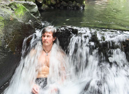 A young man sits at the base of a small waterfall relaxing as the hot thermal waters from Arenal Volcano create a silky flow over his body