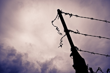 A silhouetted metal fence post with barbed wire that has been cut and left hanging against a dramatic purple hued stormy sky. Stock Photo