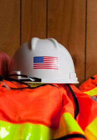 A white hard hat with the American Flag is setting on top of a orange and reflective yellow safety vest and glasses in a construction trailer.