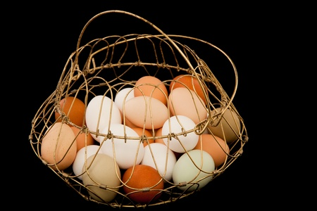 A old fashioned wire egg basket full of free range organic eggs in various sizes and colors. 版權商用圖片