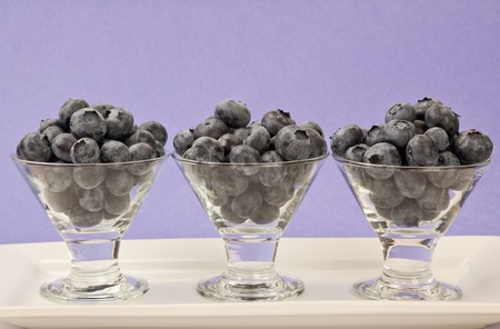 Three small glass dessert cups filled with fresh blueberries sitting on a white plate with a bluish purple background. photo