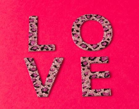 love message: Glitter covered letters in a leopard pattern spell out love in a block pattern on a bright pink paper background.
