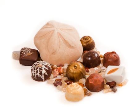 sand dollar: Un d�lar de arena hinchada rodeada de chocolates artesanales y peque�as piedras pulidas aisladas sobre fondo blanco.