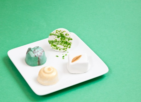 Handmade artisan chocolates arranged on a white plate with a green paper background. Stock Photo - 13177191