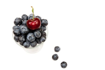 A red cherry on top of a full glass of blueberries with three berries below isolated on white background. photo