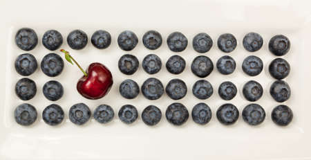 A single red cherry with a stem is placed in rows of organic blueberries on a white plate. photo