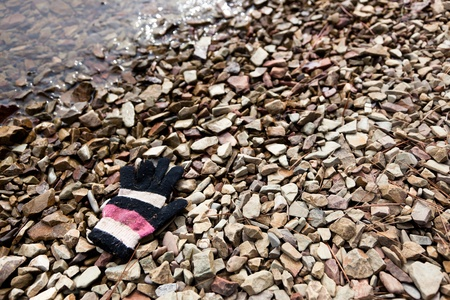 lost lake: A single striped knit glove lays on the rocky lake shore where it lost its owner. Stock Photo