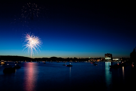 Fireworks at twilight over Lake Coeur d'Alene in Idaho with boats on the lake and city lights on the shoreline. photo
