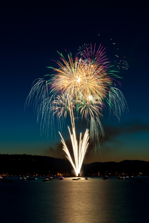 A bouquet of fireworks exploding from a barge over Lake Coeur dAlene, Idaho with the reflection showing blurred boats on the water. photo