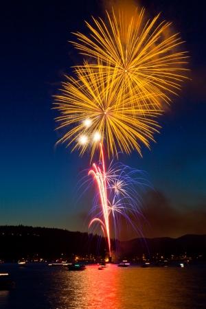 coeur: Grote helder gele vuurwerk gaan branden Lake Coeur d'Alene, Idaho in de schemering op de Fourth of July.