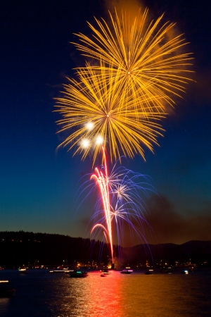 Large bright yellow fireworks light up Lake Coeur dAlene, Idaho at twilight on the Fourth of July.