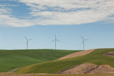 Large windmills sit atop rolling green hills to catch the wind in farming country of Eastern Washington. photo