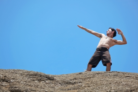 A young man stands on top of a high rock at the beach posing as a superhero. photo